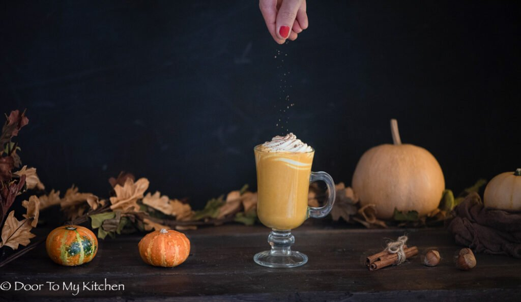 Dark and moody photo of hand sprinkling cinnamon on the top of pumpkin spice latte