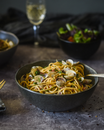 close up view of a dark and moody photo of two bowls of spaghetti with clams