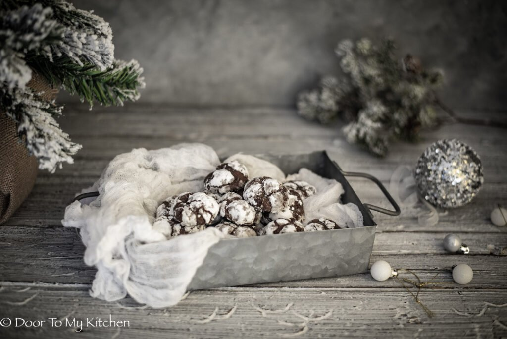 chocolate orange snowball cookies in a metal tray beside a snow sprayed Christmas tree