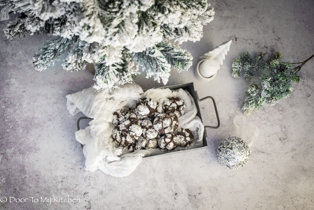 Flatlay of chocolate orange snowball cookies beside a snowy Christmas tree and silver bauble