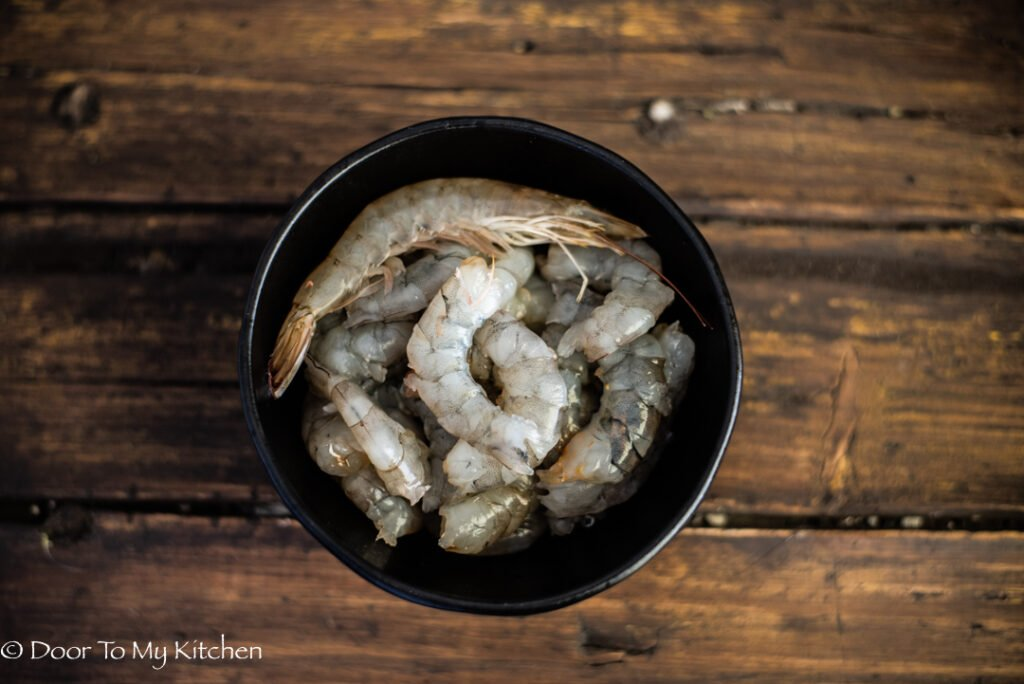 A bowl of raw deveined prawns on a wooden background