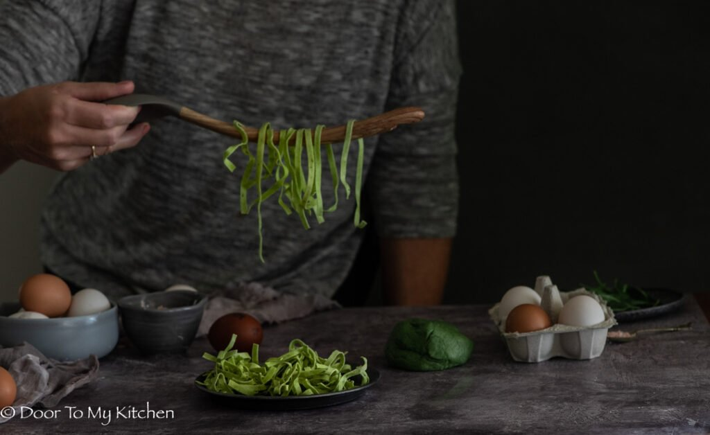 Person holding a wooden spoon with dried tagliatelli handing off it and a scene of eggs and spinach pasta dough