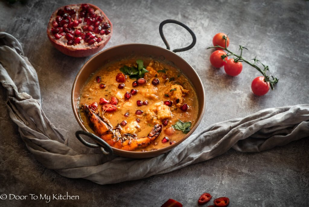 Side angel shot of a pomegranate prawn curry in a rusty curry serving dish and half a pmegranye and cherry tomatoes