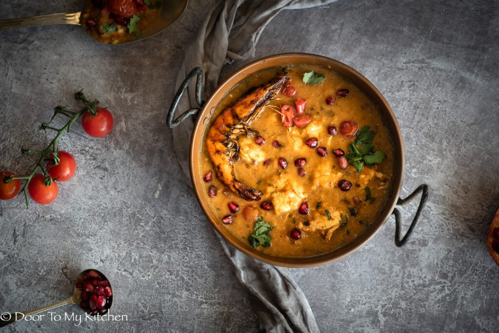 Overhead shot of pomegranate prawn curry with vine cherry tomatoes in a curry dish