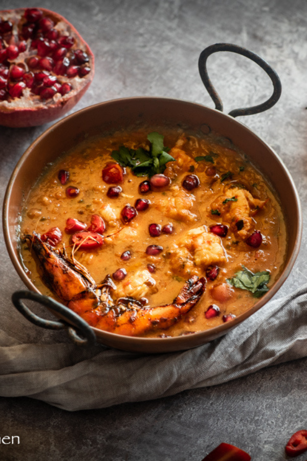 close up of pomegranate prawn curry with props beside it