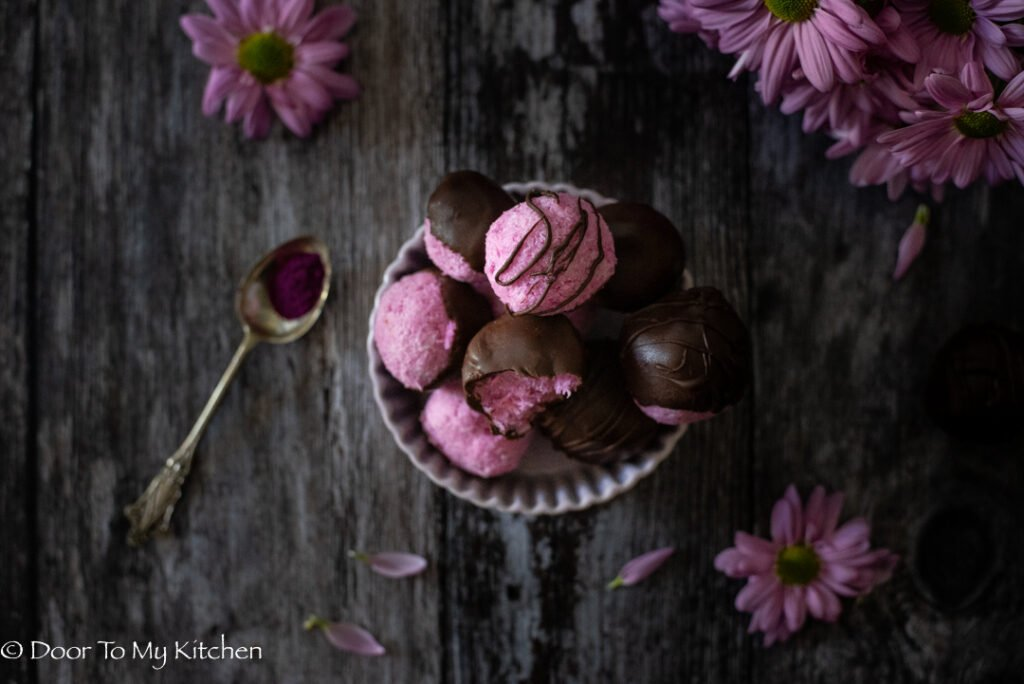 Flat lay of a bowl of pink pitaya coconut  bliss balls with pink flowers and spoon of pink pitaya powder