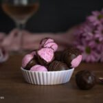 Dark and moody shot of a bowl of pink pitaya coconut bliss balls with pink flowers and a bite taken out of one