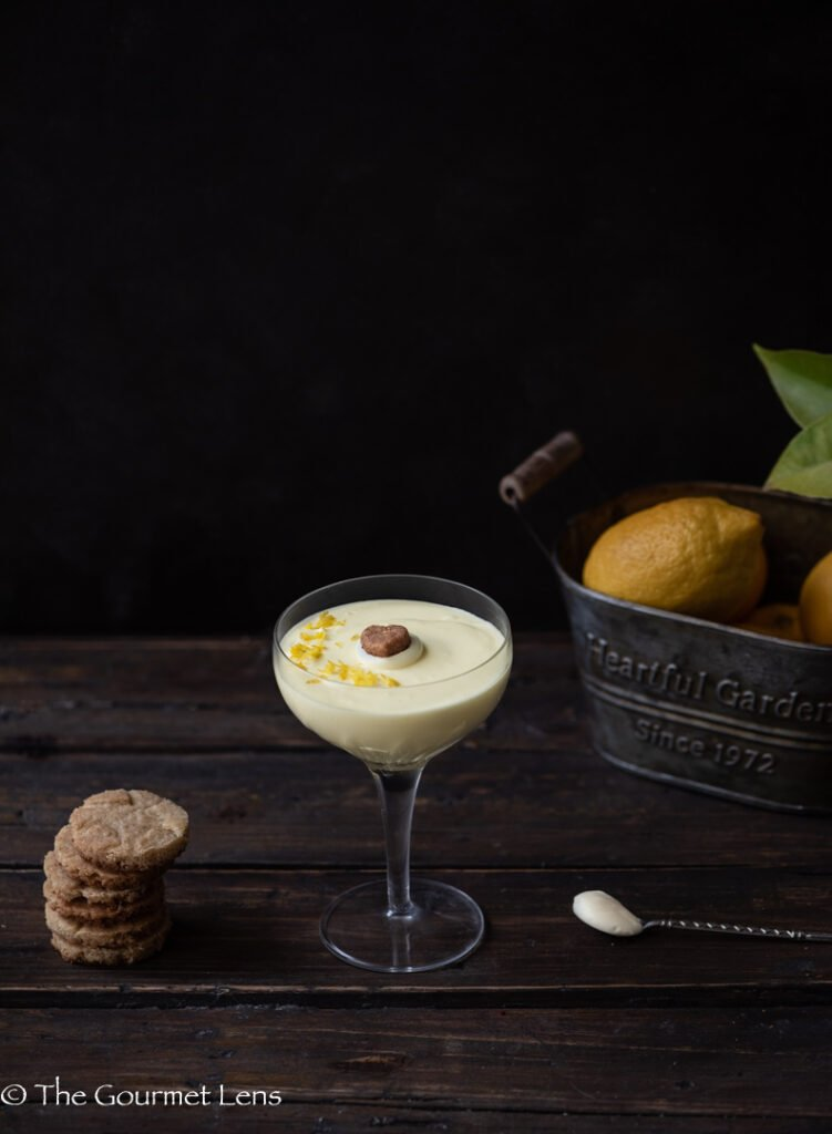 Dark and moody photo of lemon and ginger posset with ginger shortbread and a basket of lemons