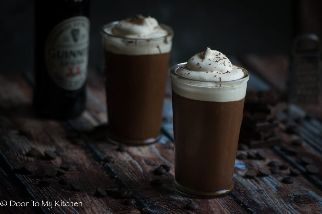 Straight on shot of Guinness Chocolate mousse topped with cream in a glass