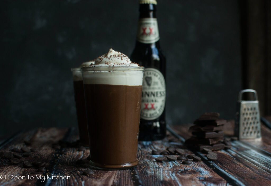 Close up of a glass of Guinness Chocolate mousse with a bottle of Guinness behind it