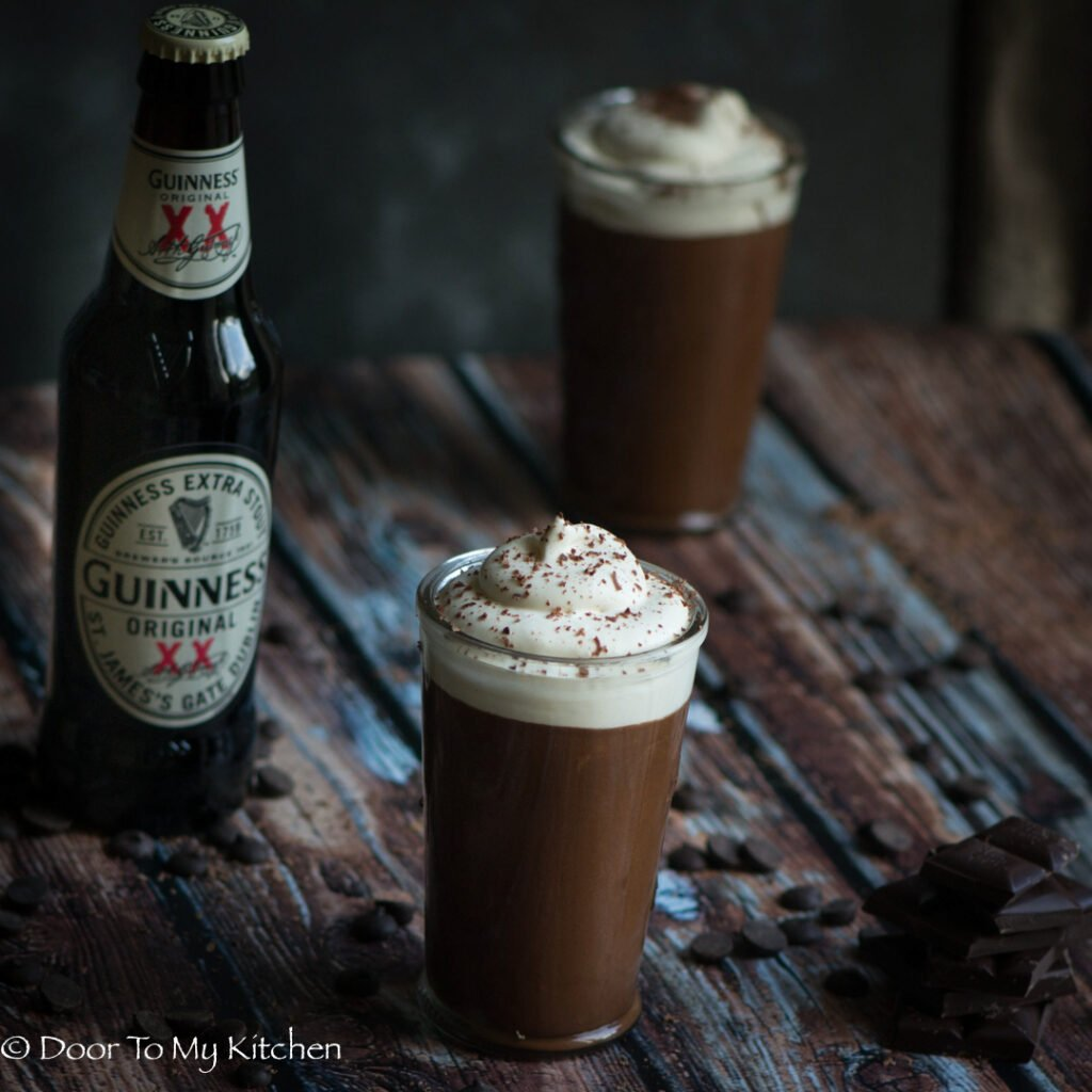 Dark and moody photo of 2 glasses of Guinness chocolate mousse beside a bottle of Guinness