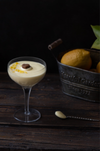 Dark and moody photo of 2 lemon and ginger possets with a rustic basket of lemons