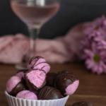 Close up of bowl of pink pitaya coconut bliss balls