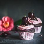 Dark and moody shot of chocolate cherry cupcakes topped with a pink swirl, fresh cherry and drizzled chocolate ganache