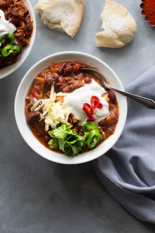 overhead angle shot of a bowl of veteran chilli with chocolate topped with sour cream and cheese and served with pitta bread